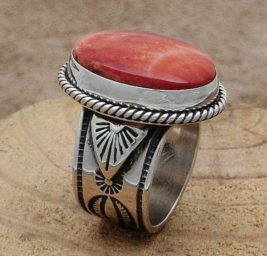 The sterling silver ring has an oval red spiny oyster shell in a smooth silver bezel with recessed silver rope trim.  The intricately stamped and oxidized sterling silver band has a raised stamped silver shield on each side.  Signed by the artist-Albert Jake, Navajo