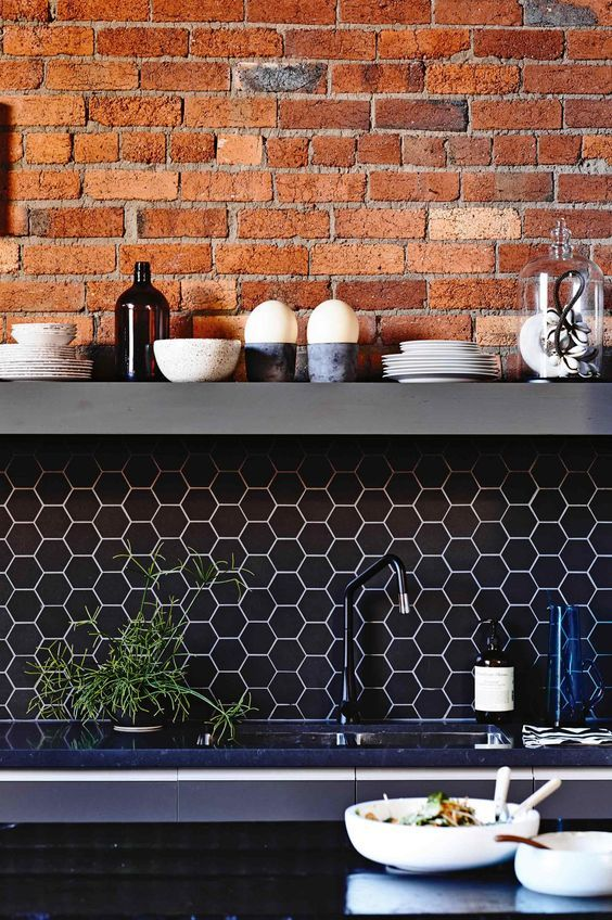 black hex tile backsplash with white grout and exposed red brick to make your kitchen stand out