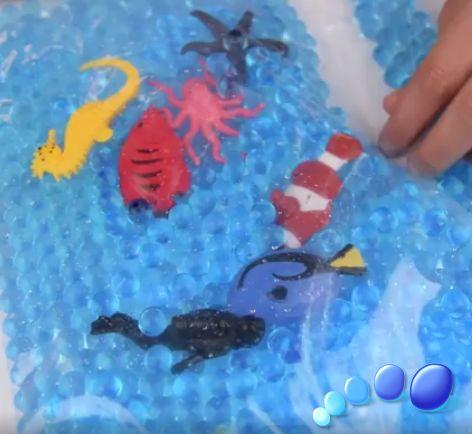 Arma tu propio acuario sensorial! Toma un bowl y agrega bastante agua. En él, pon bolitas de gel y ve como cambian su tamaño. Una vez que las bolitas ya hayan crecido, viértelas en una bolsa transparente, agrega peces, pulpos y lo que quieras para formar tu acuario! Cierra la bolsa y listo para jugar con tu pequeñ@