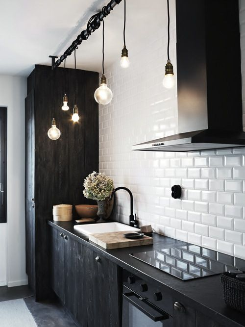black cabinets / white subway tile / industrial lightbulb lights / sleek, minimal stove top & hood