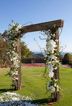 Fot a rustic wedding - wood wedding ceremony arch with white orchid and rose decor....I LOVE this....so pretty!!