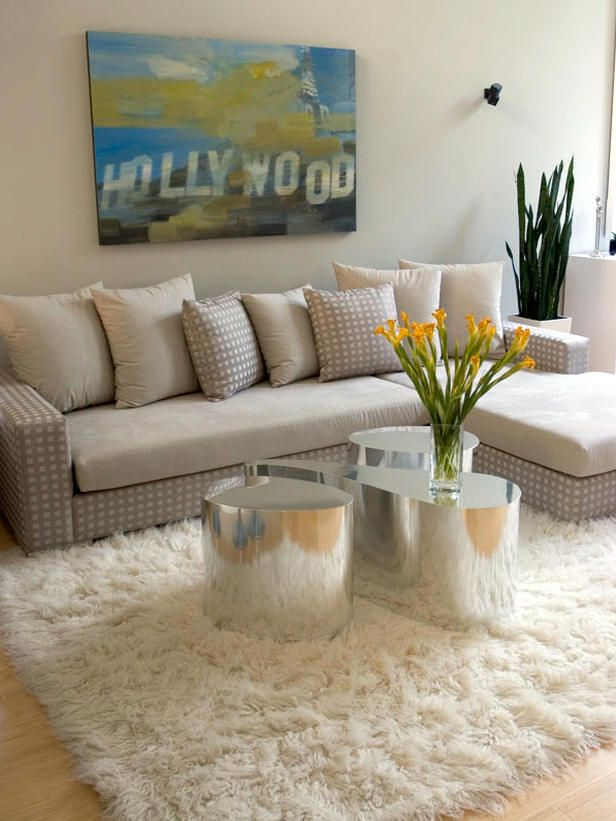 Modern whites and grays with chrome kidney tables sit atop a flokati rug in this modern space designed by Erinn Valencich.