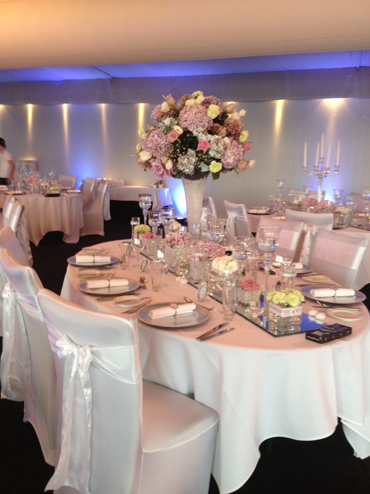 White on white chairs covers and gel ball floral vases!