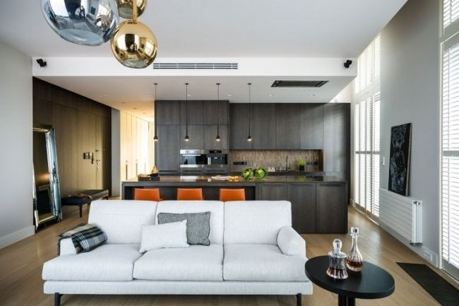une cuisine ouverte sur le salon avec un canapé blanc et suspensions design