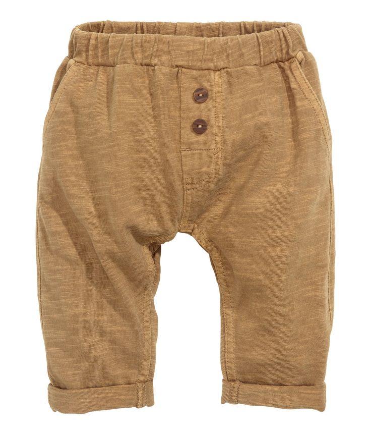 BABY EXCLUSIVE. Een broek van katoenen tricot met een onregelmatige structuur. De broek heeft elastiek in de taille, een fake gulp met knopen, steekzakken en een achterzak.