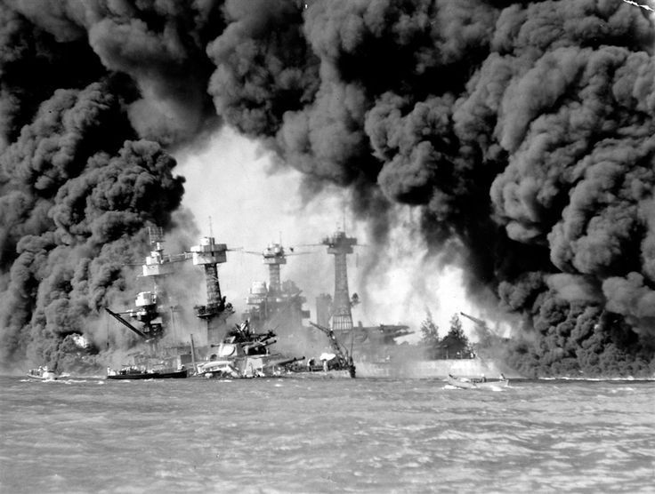 Smoke pours from wrecked American warships including (L-R) the battleships USS West Virginia & USS Tennessee which were damaged or sunk during Japanese surprise attack on Pearl Harbor.