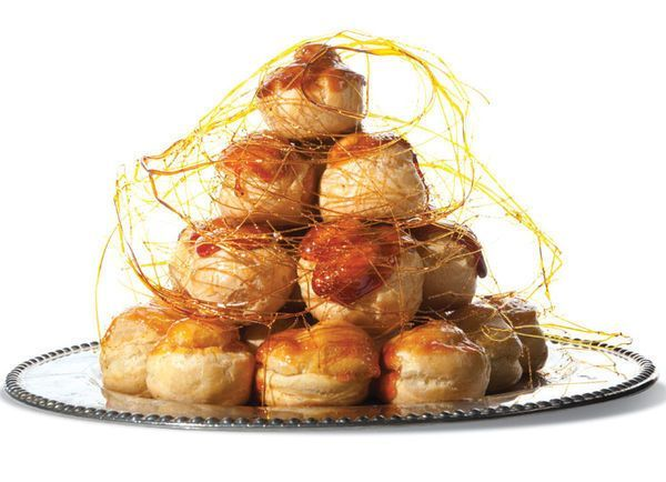 Croquembouche (Caramel-Glazed Cream Puffs) - A croquembouche is composed of profiteroles piled into a cone and bound with spun sugar. It may also be decorated with other confectionery such as sugared almonds, chocolate, and edible flowers. Sometimes it is covered in macarons or ganache. http://www.saveur.com/article/Recipes/Croquembouche