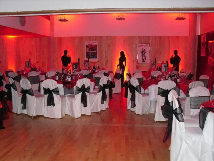 www.la-occasion.com - James Bond Themed Party  White Chaircovers with Black Organza Sash.   Black Table Cloth with Satin Red Slips on the Tables.   Spy Men and Spy Ladies Life Size Cutouts around the room