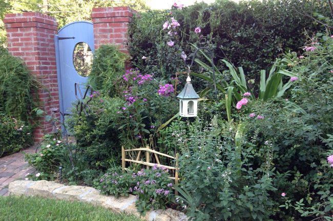 """Ce jardinier a pris des repères de traditions anglaises, et a créé coupe-off """"chambres"""" sur sa propriété.  Derrière cette porte bleue, vous trouverez un jardin de papillons.  En savoir plus sur le jardin de Barbara Baker ici »"""