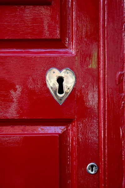 Red door with shiny heart heart shaped escuteon round the key hole