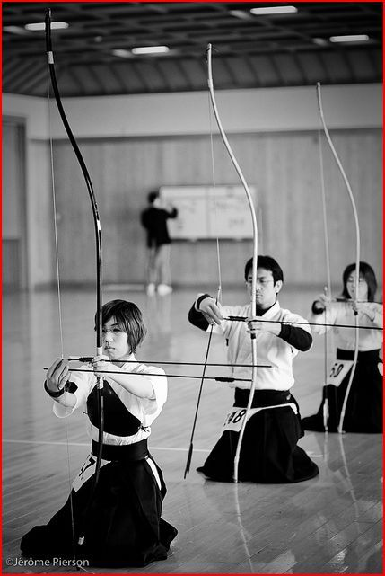 Japanese archery, Kyudo. The student archers, dressed in traditional uniforms, kneal in a line behind their instructor the dojo. They hold their bows before them and practice the kyudo method of knocking the arrow. Japan, circa late 1990s to early 2000s.