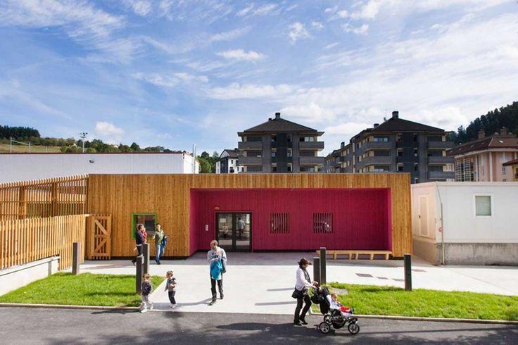 New Building for Nursery and Kindergarten in Zaldibar, Spain | The nursery entrance features fuschia colour + the kindergarten green