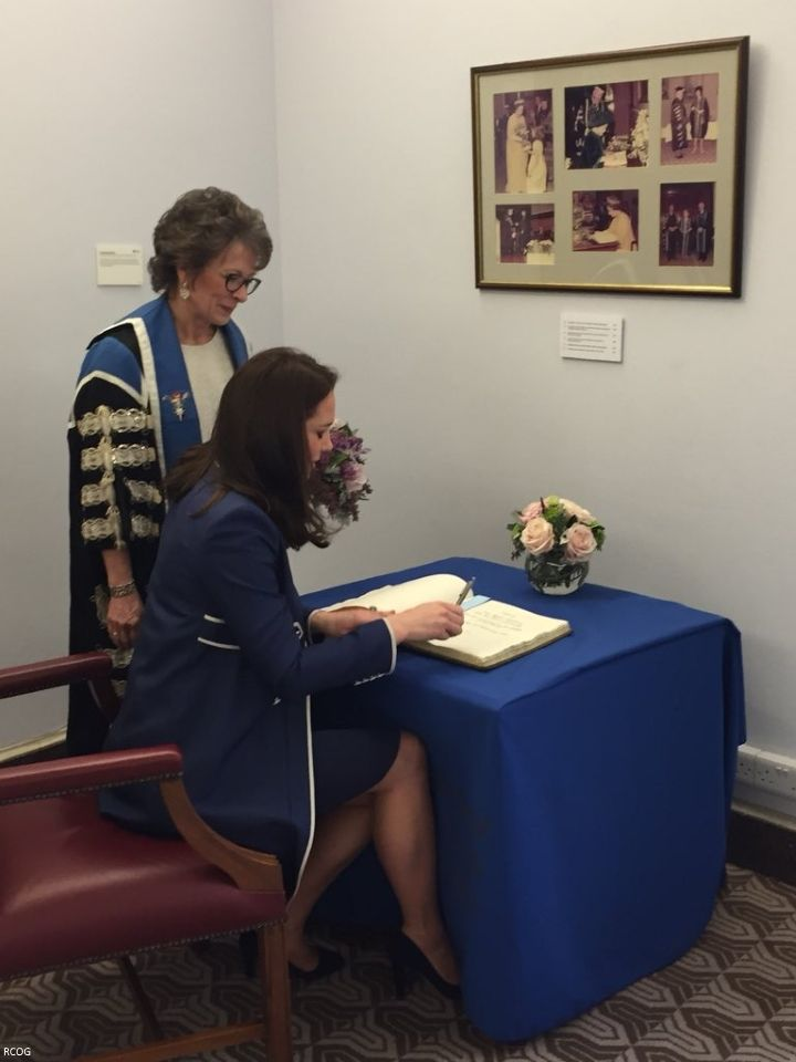 hrhduchesskate: Royal College of Obstetricians and Gynaecologists, London, February 27, 2018-The Duchess of Cambridge signs the visitors' book at RCOG beneath pictures of the first Royal Patron the Queen Mother