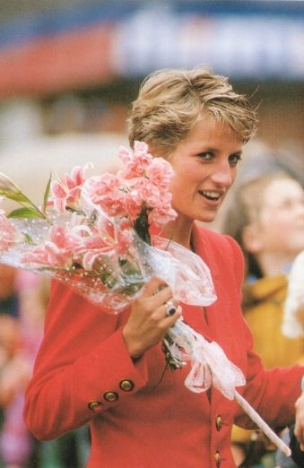 Princess Diana on a red jacket or blazer, gold coloured buttons. Circa 1987-1990. Looks like spectators in the background, so Wimbledon or football maybe. Given flowers: pink lillies, pink carnations.