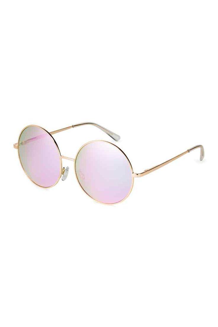 Zonnebril: Een zonnebril met een metalen montuur en grote, ronde, getinte glazen met uv-bescherming.