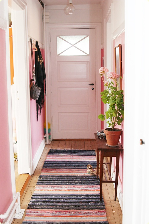Although I don't like the pink walls, but well used space with mirror, narrow console and a stripped rug to give illusion of wider space for a narrow hallway.