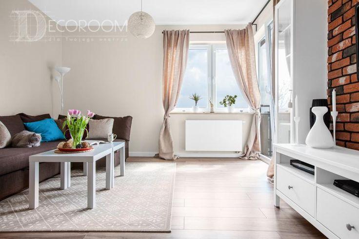 Salon w stylu prowansalskim. Beżowe ściany w salonie eksponują białe meble i dodają wnętrzu ciepła oraz przytulności. Ażurowy klosz pięknie rozprasza światło po zmroku, a ściana z czerwonej cegły w centralnym miejscu eksponuje telewizor i nadaje wnętrzu wyjątkowy charakter.