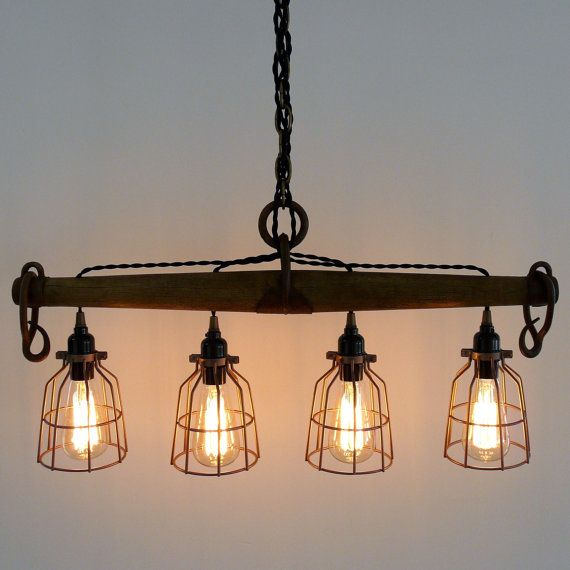 This modern rustic light, featuring four bulbs, is crafted from a genuine antique singletree yoke. This industrial looking light would look great