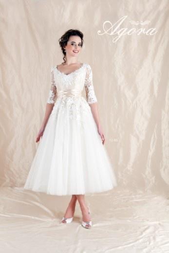 Tea length white dress with longer sleeves.