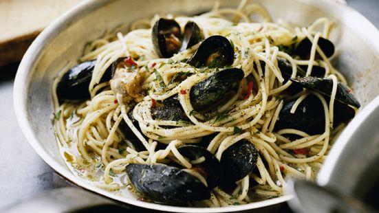 Rensa och tvätta musslorna och kasta de som inte är hela och stängda. Koka pastan enligt anvisning på paketet. Fräs vitlöken i olivolja utan att ta färg. Häll på vinet och låt koka upp. Tillsätt musslorna och koka på stark värme ca 2 minuter under lock tills alla musslorna öppnat sig. Släng de som inte öppnat sig. Lyft upp musslorna och låt buljongen koka ihop 2 minuter och smaka av med salt, svartpeppar och citronsaft. Häll i nykokt pasta, musslor, chili.