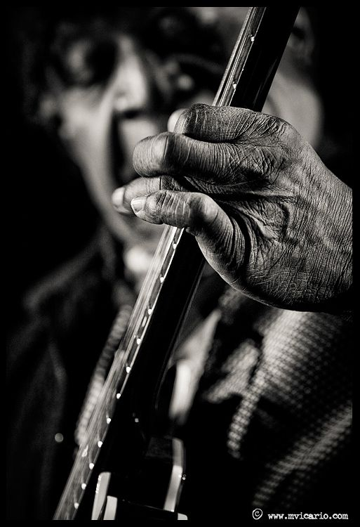 fingers on the fret board. hands in focus, guitarist's face is a secodary subject and out of focus