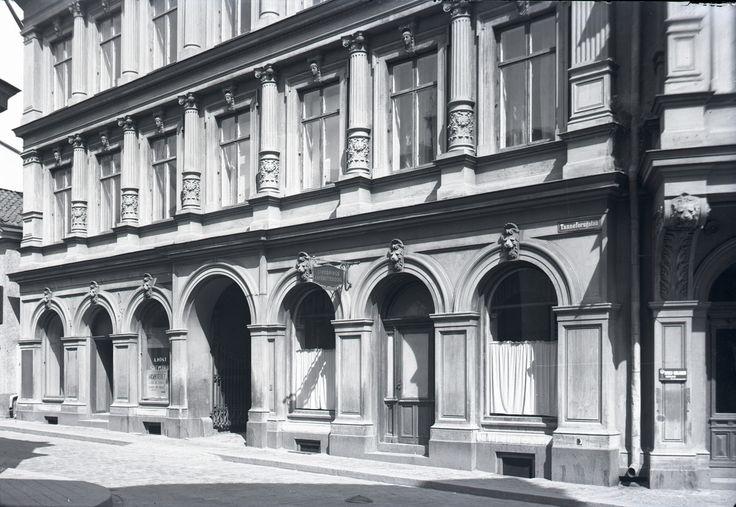 Tanneforsgatan 1. LInköpings Kaféaktiebolag och A. Röst Skomakeri finns i byggnaden. Det avskalade huset: Byggmästaren Oskar Nylander uppförde detta boningshus 1885, arkitekt S.H. Gratz. Vid en ombyggnad 1939 skalades fasaden mot Trädgårdstorget för att smälta in i den omgivande bebyggelsen, samtidigt påbyggdes huset med en våning.