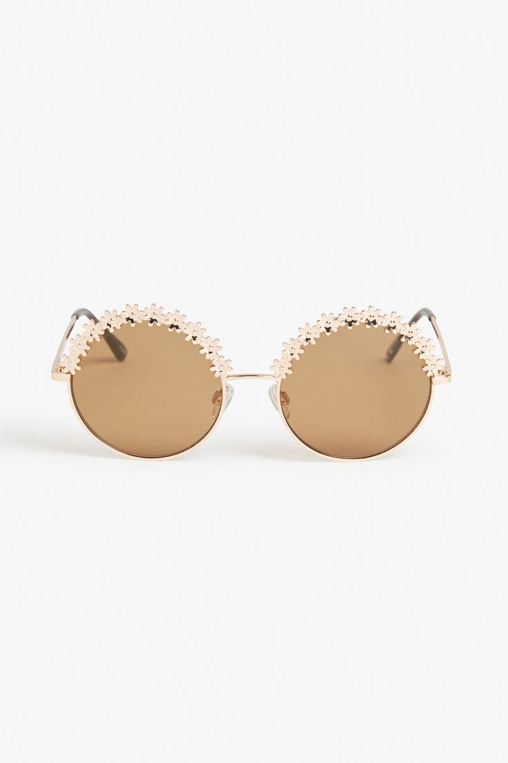 Round, rosy gold hippie sunglasses with daisies rimming the top. Brown lenses and tortoise-y temple tips.