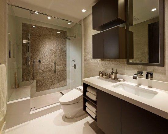 Banheiro com parede em pedra e marcenaria em madeira escura
