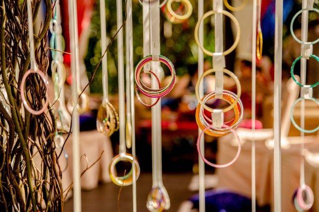 Brightly coloured bangles hanging off ribbons! #DIY #indian #wedding #decor #idea