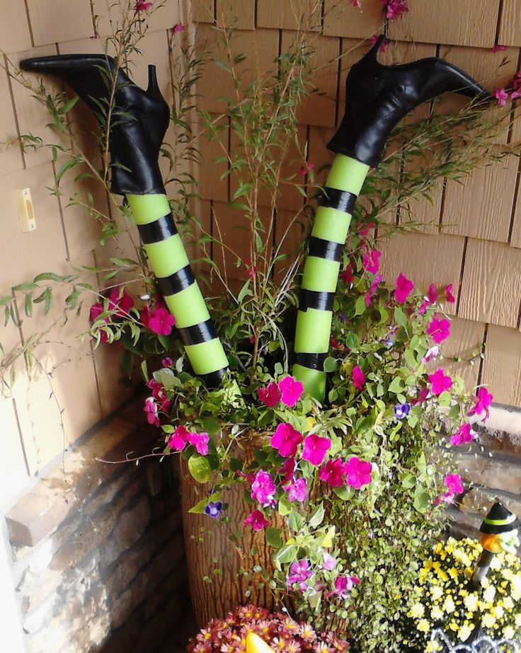 A swim noodle, electric tape, and a cheap pair of boots from the consignment store add halloween whimsy  to your flower pot in 10  minutes!