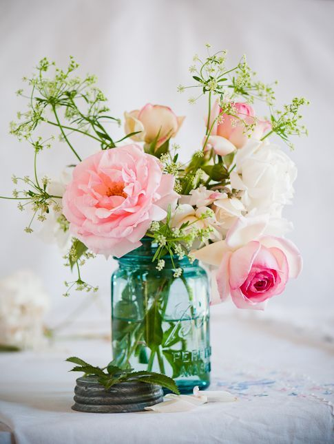 The cocktail tables will feature blue mason jar filled with blush spray roses, mint green eucalyptus and gray dusty miller.