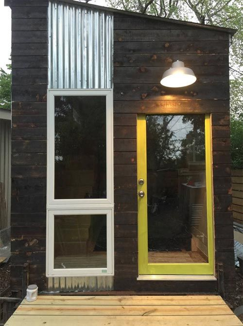 This modern style tiny house has a bedroom loft with a queen size bed, a sofa bed, and a small kitchenette with a refrigerator, sink, and coffee maker.