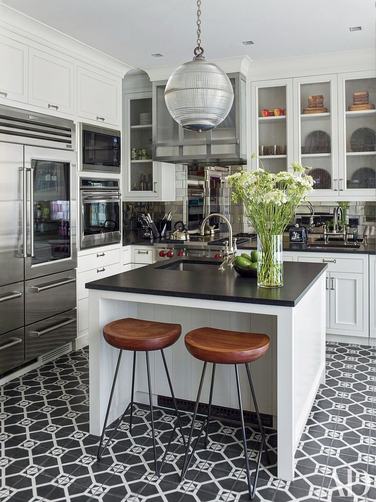 The updated kitchen features a striking antiqued-mirror backsplash…
