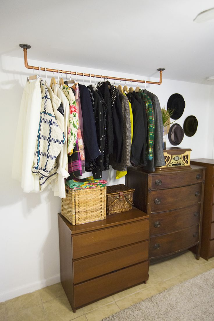 Hanging Copper Pipe Clothing Rack DIY (click through for tutorial) - If you don't need the extra storage space, but you love how this rack looks, you can use it to hang your plants or to hang your art. Also, you could have it coming out from the wall instead of hanging from the ceiling to create a little organized art section for your kiddos. All you need are a few baskets, and s hooks. This project is so easy to make and can work in any room!