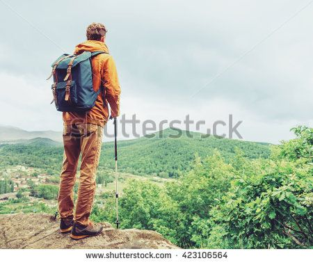Hiker young man with backpack and trekking poles standing on edge of cliff and…