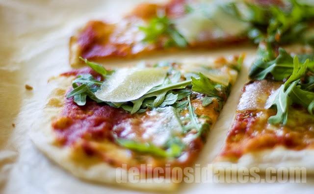 Pizza de rúcula y parmesano  Una nueva favorita llena de sabor y contrastes: La pizza de rúcula y parmesano. Por un lado el sabor amargo de la rúcula y su textura crujiente (se añade cruda tras hornear la pizza) y por otro el de lascas de parmesano con su sabor recio y ligeramente picante.