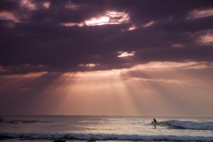 Lone surfer in sea with sunlight streaming through clouds.