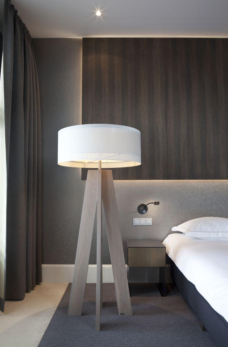 Diverse soorten verlichting toegepast in een slaapkamer, nachtlampje/leeslicht, indirecte verlichting, plafondspots en een staande vloerlamp.