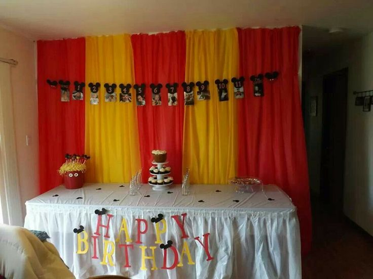 Mickey mouse birthday. Dollar store table covers with holes punched every couple inches, on thread for backdrop.