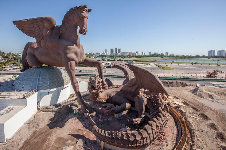 """Strassacker errichtete auf dem Gelände des Gulfstream Parks in Hallandale Beach (Miami, Florida) die größte Pferdeskulptur der Welt aus Bronze. Auftraggeber ist das Unternehmen """"Gulfstream Park"""". Die Bronze-Skulptur """"Pegasus"""" (inkl. Drachen) ist 33 Meter hoch, 60 Meter lang und 35 Meter breit. Innerhalb dieser Bronze-Skulptur befindet sich eine höchst komplizierte Stahlkonstruktion für die Statik."""