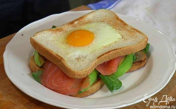 На обжаренный целый кусок хлеба выложить салат, ломтики авокадо, семгу и накрыть куском хлеба с яйцом.