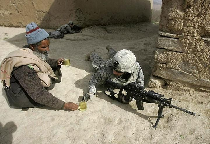 An Afghan man offers tea to soldiers