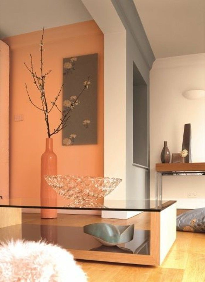 orange and white and grey walls, inside room with light laminate flooring, living room color ideas, modern table with glass top, large decorative vase, and crystal bowl