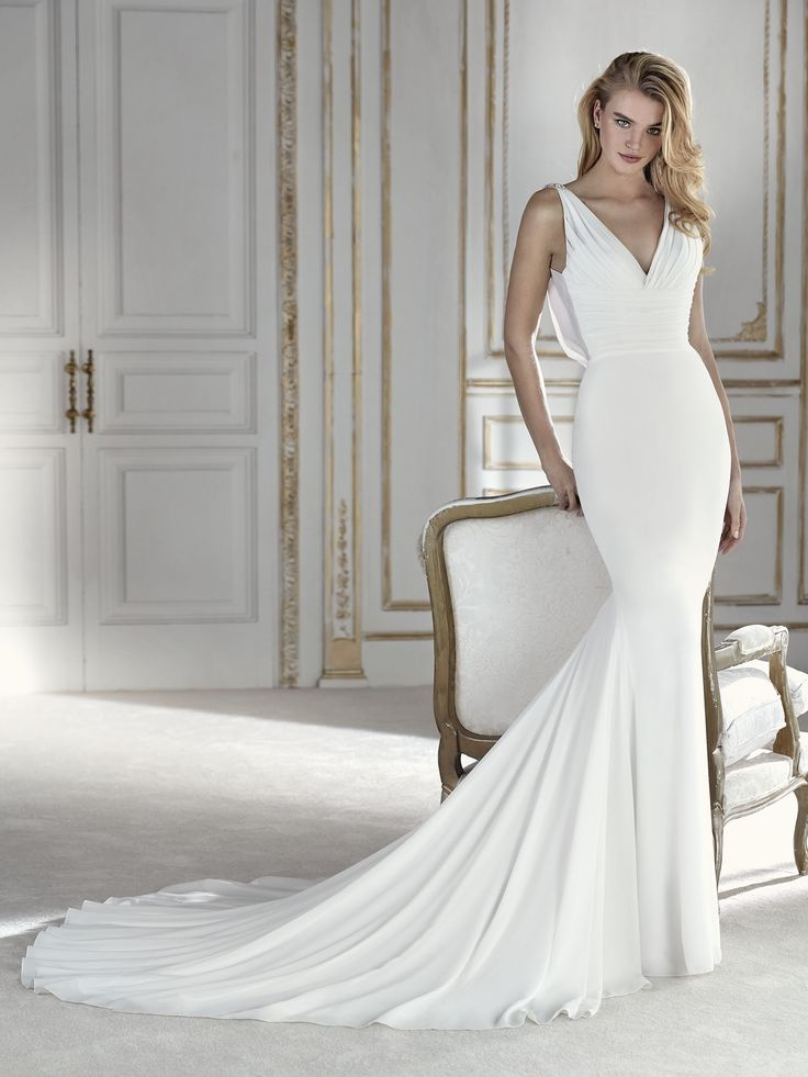 This is one of those dresses you'll fall in love with at first sight. A very elegant mermaid design in georgette, a very flowing fabric with plenty of movement. A form-fitting wedding dress that accentuates the femininity of the body's curves, with a draped V-neck that is gathered at the waist. And a spectacular jewelry detail on the back that complements the draped V-neck with a wonderful cascade of gemstone chains that gives the dress lots of sparkle, style and personality.