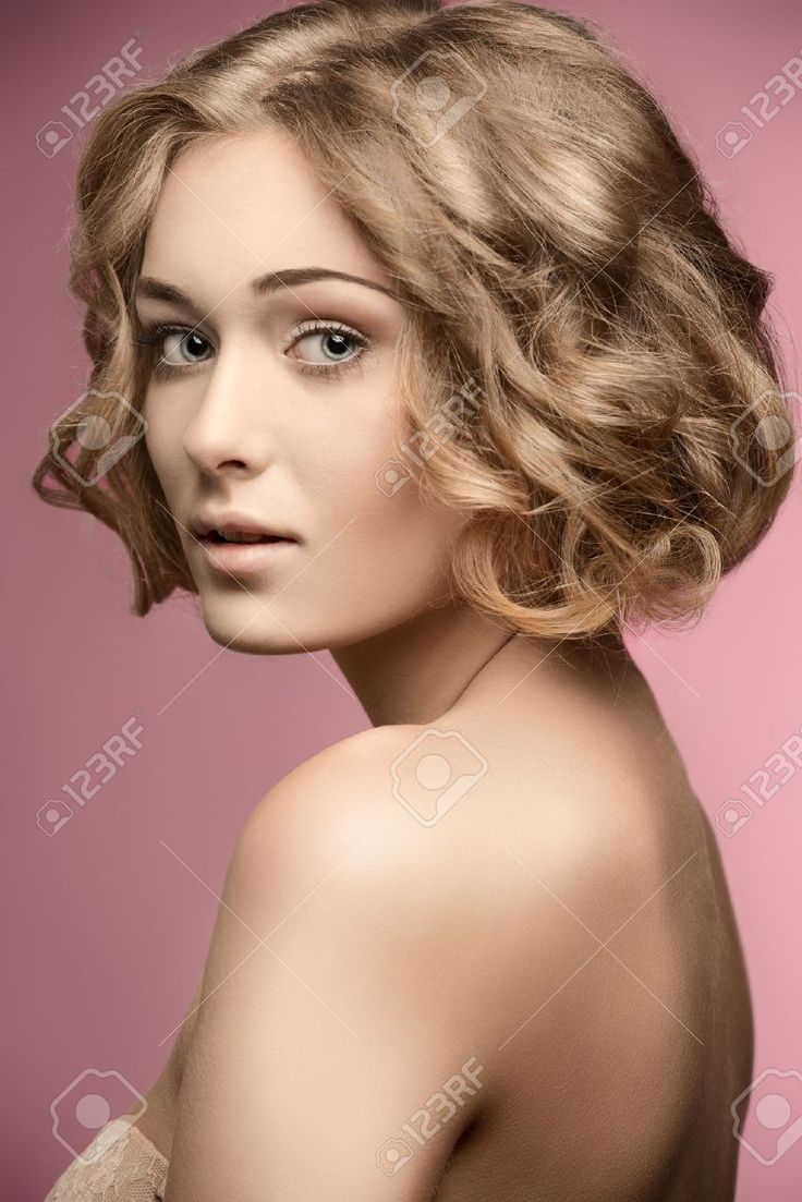 Schöne Blondine, die mit gelocktem Bob Haircut And Natural aufwerfen