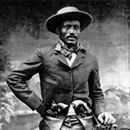 """Born a slave in Arkansas in 1849, Ned Huddleston (a.k.a Isom Dart) gained a reputation for being a notorious Wyoming Territory outlaw and rustler. Huddleston was on of the best riders, ropers, and bronco-buster known of his time. Many people also knew the black cowboy by the names """"Black Fox."""""""