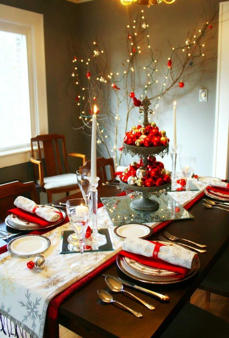 présentoir à cupcakes décoré de boules de Noël en rouge et or, chemin de table à motif flocon de neige et chandelles blanches