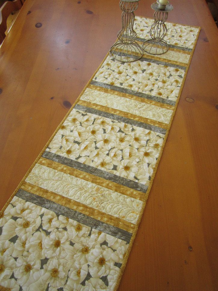 Decorate your table beginning with this beautiful floral table runner. This runner has flowers in the main fabric with complementary fabrics between. This runner is a beautiful piece to display on you