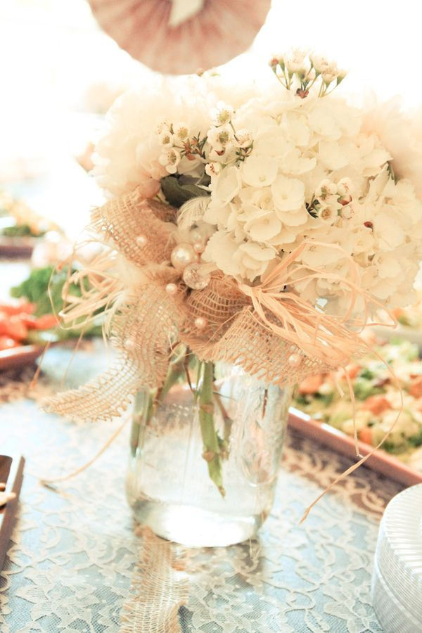 Mason jar with short cut flowers, tied with raffia and a strip of beaded burlap, sitting on a lace tablecloth. So sweet.