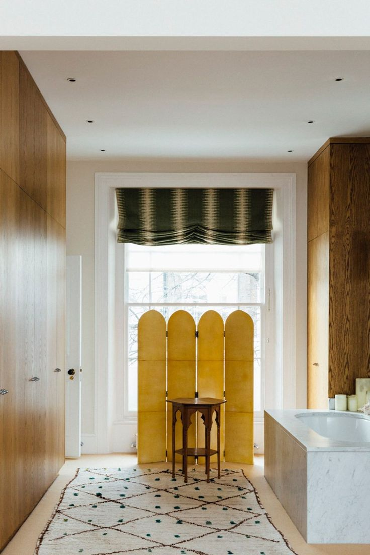 """The bathroom in [link url=""""http://www.houseandgarden.co.uk/interiors/real-homes/sarah-graham-home-and-studio""""]the home of artist Sarah Graham[/link] is furnished with an Italian vellum screen from [link url=""""http://roseuniacke.com/""""]Rose Uniacke[/link], a side table from [link url=""""http://www.jamesgraham-stewart.com/""""]James Graham-Stewart[/link] and a rug from [link url=""""http://www.shahbazafridi.com/""""]Shahbaz Afridi[/link]. [i]Taken from the October 2016 issue of House & Garden.[/i] Like…"""